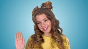Chica joven hermosa en una camisa amarilla que agita su mano y que sonríe mientras que mira en la cámara metrajes