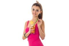 Chica joven hermosa en una camisa rosada que sonríe y que sostiene un vidrio de zumo de fruta Imágenes de archivo libres de regalías