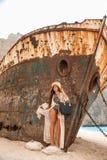 Chica joven hermosa en una playa con el naufragio Fotos de archivo