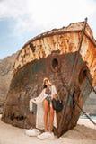 Chica joven hermosa en una playa con el naufragio Foto de archivo libre de regalías