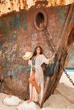 Chica joven hermosa en una playa con el naufragio Imagen de archivo libre de regalías