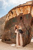 Chica joven hermosa en una playa con el naufragio Foto de archivo