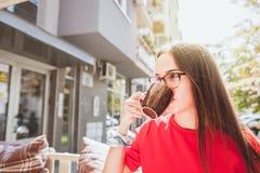 Chica joven hermosa en vestido rojo y las lentes que sostienen la taza con su mano y que beben el café mientras que ella que sien imagen de archivo libre de regalías