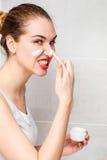 Chica joven hermosa enojada que aplica la molestia cuidando la crema de cara en exceso Imagen de archivo