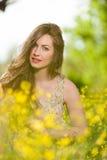 Chica joven hermosa entre las flores amarillas Foto de archivo