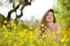 Chica joven hermosa entre las flores amarillas Imagenes de archivo