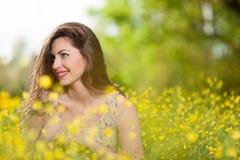 Chica joven hermosa entre las flores amarillas Imágenes de archivo libres de regalías