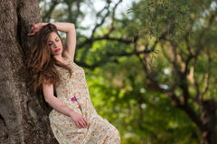 Chica joven hermosa entre las flores amarillas Foto de archivo libre de regalías