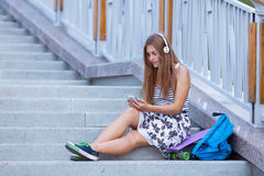 Chica joven hermosa, feliz con el smartphone que se sienta en las escaleras Foto de archivo libre de regalías