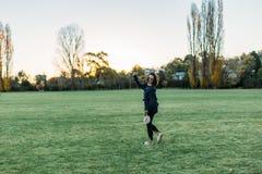 Chica joven hermosa feliz que corre en un campo Imagenes de archivo