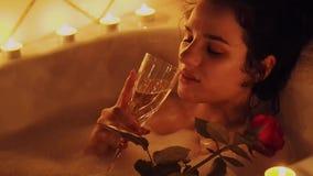 Chica joven hermosa feliz que miente en el cuarto de baño con espuma con una rosa en su mano y champán de consumición almacen de video
