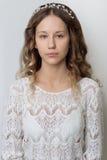 Chica joven hermosa joven con el pelo rizado largo, ningún maquillaje con una cara limpia con una guirnalda en su retrato princip Foto de archivo