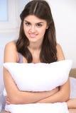 Chica joven hermosa que abraza la almohada Imagen de archivo