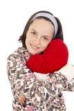 Chica joven hermosa que abraza la almohada de la dimensión de una variable del corazón Foto de archivo