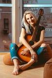 Chica joven hermosa que abraza una guitarra con las manos y las sonrisas en t Foto de archivo libre de regalías