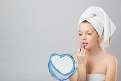 Chica joven hermosa que aplica el lápiz labial en el espejo Fotografía de archivo libre de regalías