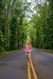 Chica joven hermosa que camina abajo del camino Imagenes de archivo