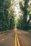 Chica joven hermosa que camina abajo del camino Foto de archivo libre de regalías