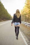 Chica joven hermosa que camina abajo del camino en el bosque Imagenes de archivo