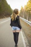 Chica joven hermosa que camina abajo del camino en el bosque Imágenes de archivo libres de regalías