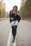 Chica joven hermosa que camina abajo del camino en el bosque Imagen de archivo libre de regalías