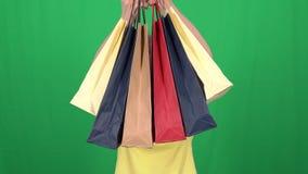 Chica joven hermosa que celebra bolsos que hacen compras multicolores y la sonrisa almacen de video