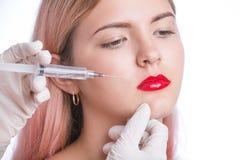 Chica joven hermosa que consigue la inyección cosmética en labios Aislado en gris Foto de archivo