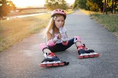 Chica joven hermosa que descansa después de paseo en pcteres de ruedas en el parque Fotos de archivo libres de regalías