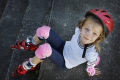 Chica joven hermosa que descansa después de rollerblading en el parque Fotos de archivo