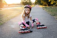 Chica joven hermosa que descansa después de rollerblading en el parque Foto de archivo