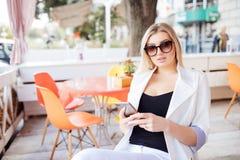 Chica joven hermosa que descansa en un café modelo rubio atractivo que se sienta con una taza de café en un café al aire libre de Imagen de archivo