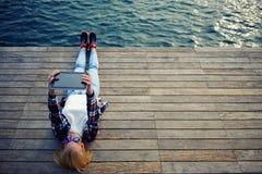 Chica joven hermosa que descansa sobre un embarcadero en el primer día que soporta la tableta del verano que soporta la tableta Imagenes de archivo
