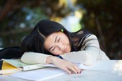 Chica joven hermosa que duerme con una sonrisa encantadora en la tabla Imagenes de archivo