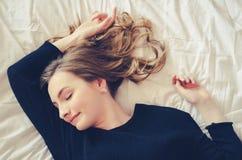Chica joven hermosa que duerme en el dormitorio Imagenes de archivo