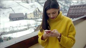 Chica joven hermosa que escribe un mensaje de texto en el teléfono almacen de metraje de vídeo