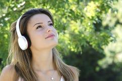 Chica joven hermosa que escucha la música Fotografía de archivo libre de regalías