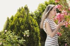 Chica joven hermosa que goza del olor de flores Imagen de archivo libre de regalías