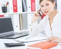 Chica joven hermosa que habla en el teléfono móvil que se sienta en la oficina Negocio, oferta de trabajo, investigación del anal Fotos de archivo