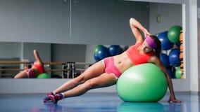 Chica joven hermosa que hace ejercicios con la bola del ajuste en el gimnasio del deporte Imagenes de archivo