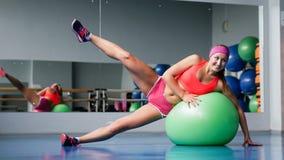 Chica joven hermosa que hace ejercicios con la bola del ajuste en el gimnasio del deporte Foto de archivo libre de regalías