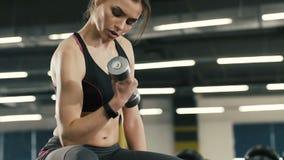 Chica joven hermosa que hace ejercicios con los dumbbels en el fondo del gimnasio almacen de metraje de vídeo