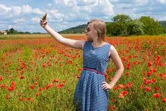 Chica joven hermosa que hace el selfie con el teléfono móvil en una amapola Imagen de archivo