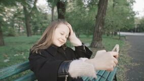 Chica joven hermosa que hace el selfie que se sienta en un banco en el parque almacen de video