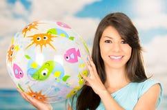 Chica joven hermosa que juega con la pelota de playa Fotografía de archivo