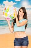 Chica joven hermosa que juega con la pelota de playa Imagen de archivo libre de regalías