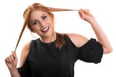 Chica joven hermosa que juega con su pelo Imagen de archivo