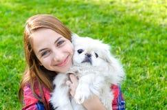 Chica joven hermosa que juega con su perro Imagen de archivo