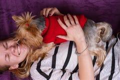 Chica joven hermosa que juega con su terrier de Yorkshire en casa que coloca Imagen de archivo