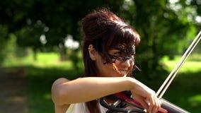 Chica joven hermosa que juega en el violín eléctrico en parque hermoso metrajes