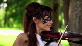 Chica joven hermosa que juega en el violín eléctrico en parque hermoso almacen de metraje de vídeo